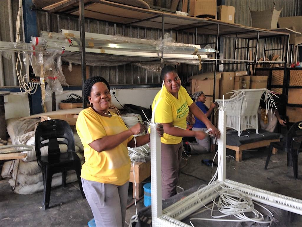 Two happy ladies weaving the Malindii dining table
